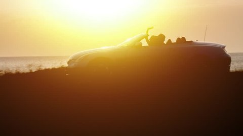 Silhouette Of Convertible Cabriolet Car Driving On Seaside At Sunset Couple On Vacation Sunset Travel Holiday Trip Love Adventure Sunshine Golden Hour Drone Tracking Shot
