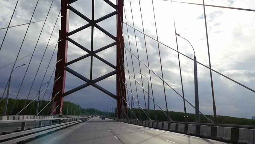 Road through the bridge with cloudy sky and moving cars in slowmotion. 1920x1080 | Shutterstock HD Video #19061266