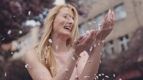 Gorgeous blonde girl is holding pink flower petals in her hands, playing with flower petals. Smiling. Blowing petals, windy weather. Female portrait. Outside shooting. Close up view, slow motion.