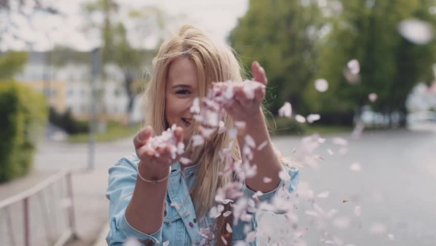 European young blonde attractive girl is moving down the park, then she turns and throws the petals of cherries blossom towards the camera. Waving hear. Building like castle. Green bushes and trees.