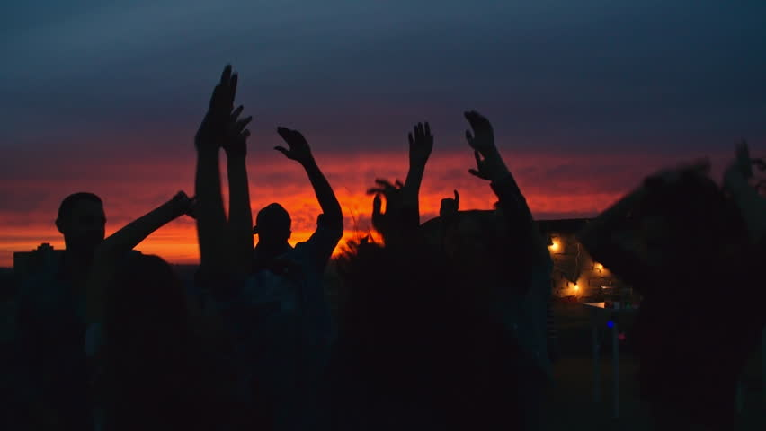 Silhouettes of group of young people dancing and raising their arms up in the air against beautiful sunset sky at rooftop party