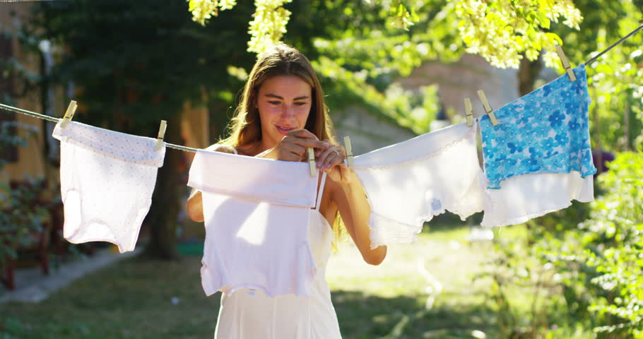 Slow motion of a young housewife woman is hanging just washed clean  laundry on clothesline outside her house in a sunny day. concept of sustainability, nature and purity and deep clean after washing.