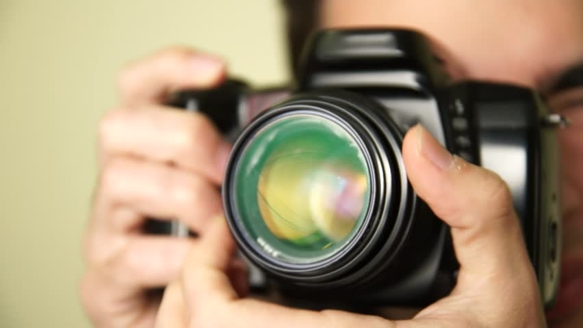 Photographer takes pictures with DSLR camera.