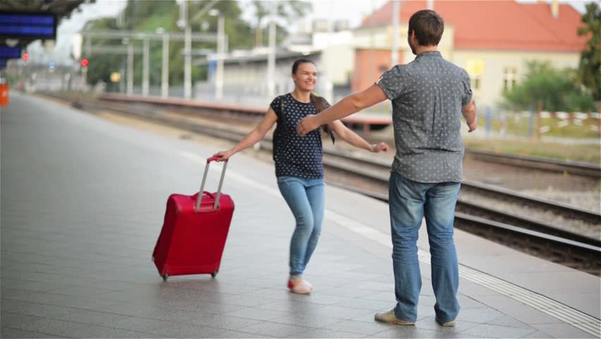 Young couple happy to meet again in the train station, girl runs to meet her boyfriend and throws a suitcase, twist on hands