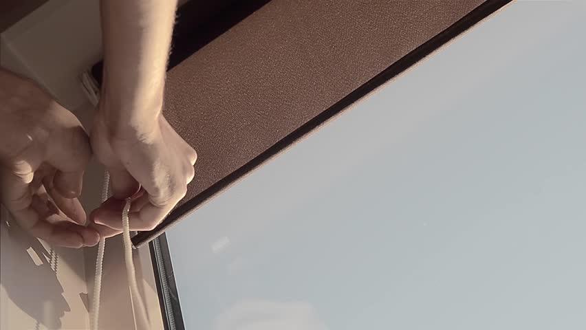 Hand closes roller blinds on the window. Window accessory