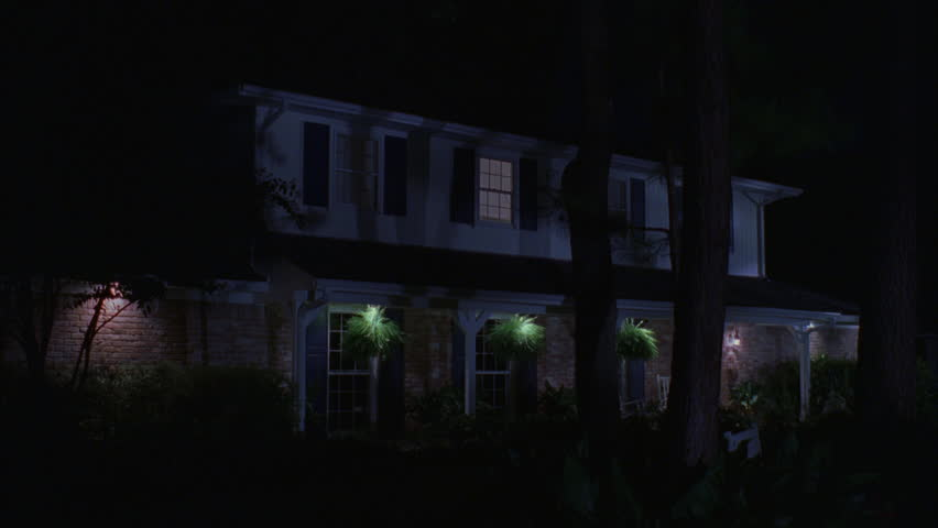 night Across bushes trees, Raked left upscale 2 story house, brick white wood Large porch, yard All lights upstairs windows turn off, one back font color black [Requires Clearance series offers only]
