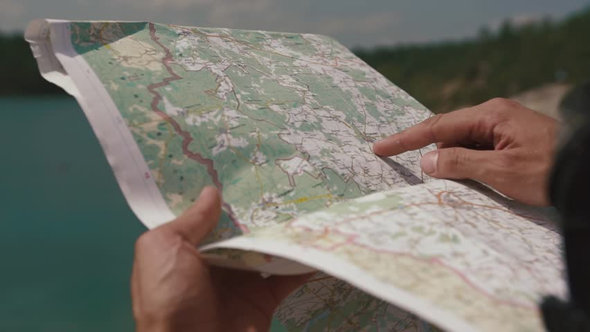 Man's hand drawing on map by finger, checking way when looking to lake ahead