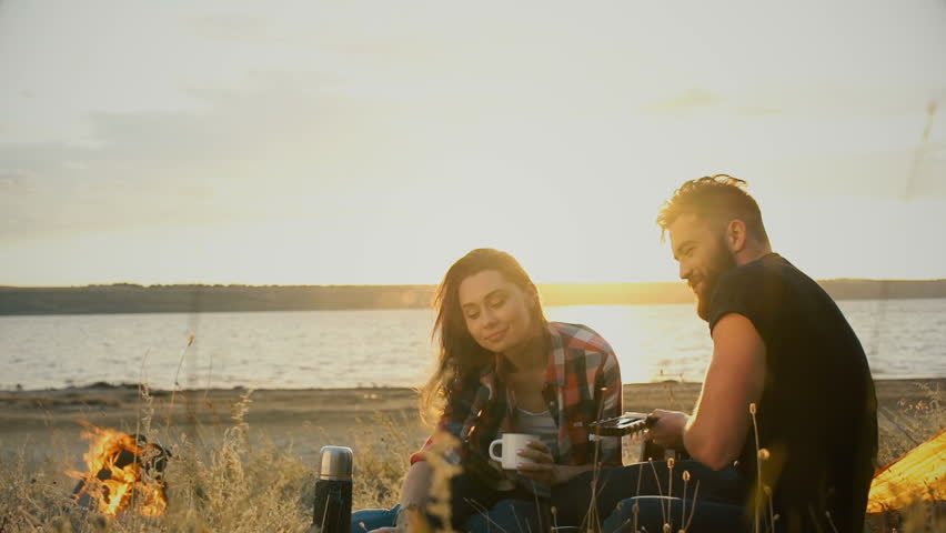 Young beautiful couple in love having drinks while sitting at the camp tent at sunset