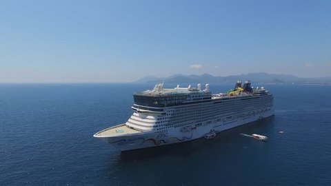 CANNES, FRANCE - JUL 28, 2016: Cruise liner Norwegian Epic with rescue boats sail not far from coastal city at summer sunny day. Aerial view