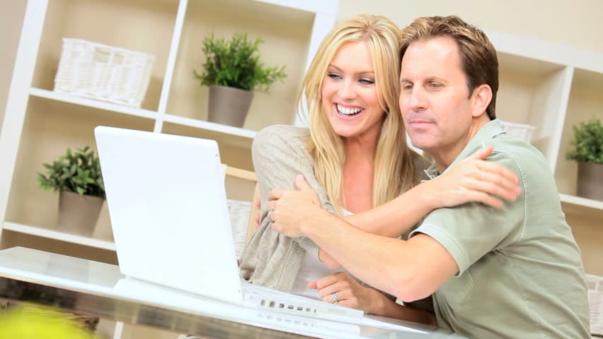 Young caucasian couple with laptop excited to see the results of their online success