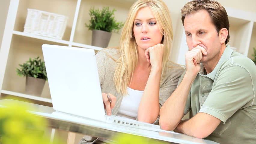 Young couple at home with laptop trying to find solutions to financial problems | Shutterstock HD Video #1925686