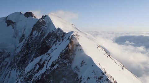 Slow Mo Aerial shot flying over a ridge of a snowy peak in the sun with clouds below and avalanche cracks in the distance (Courmayeur, Aosta Valley/Italy - March, 2016)