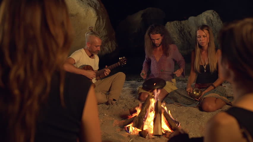 Friends speaking, smiling, playing on instruments, sitting near bonfire at night beach. Slow motion. #19264396