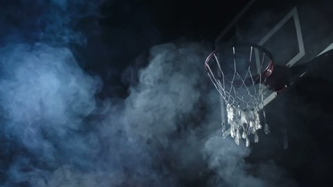 Basketball player jumping in the air and performing reverse dunk in the dark court in slow motion with smoke in the background