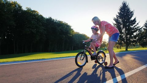 Mom plays with her daughter, teaching her to ride a bicycle. At sunset background
