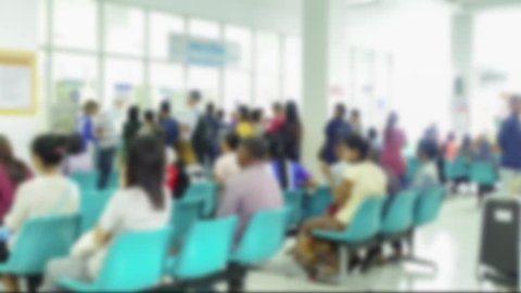 Blurred image of unidentified people and patient in hospital waiting medicine or doctor time-lapse.