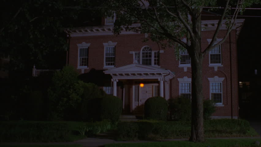 night wide hold nice eastern two story house, all red brick colonial house, white trim, dormers, portico, only porch light on, attic