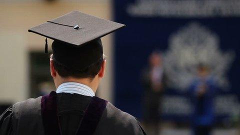 Male graduate listening to university rector's speech at graduation ceremony
