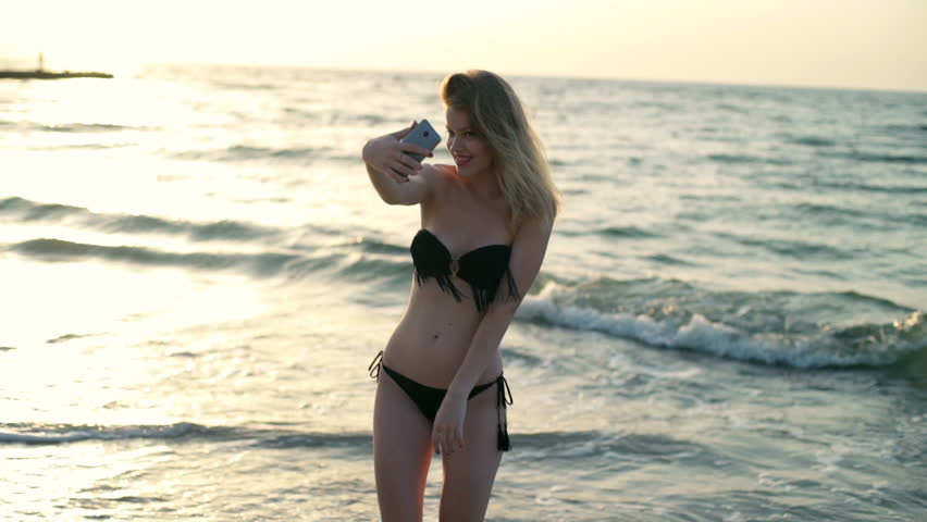 Young beautiful girl in swimwear smiling, making selfie at beach, sea background