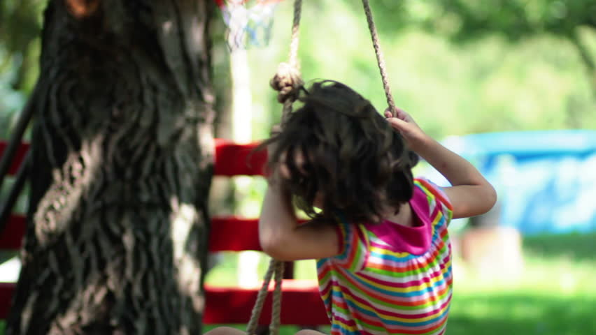 Young little  girl spinning in a tree swing and smiling