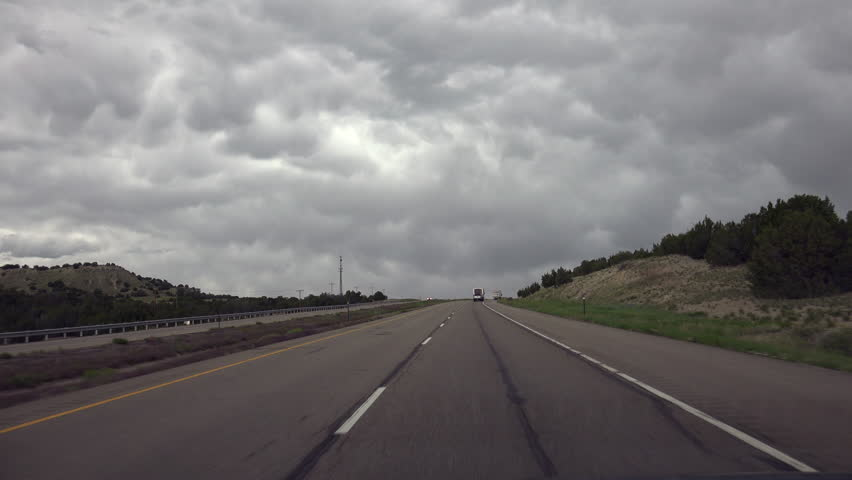 Sky filled with lumpy, bumpy storm clouds hangs over interstate freeway, driving POV. 4K UHD 3840x2160 | Shutterstock HD Video #19449415