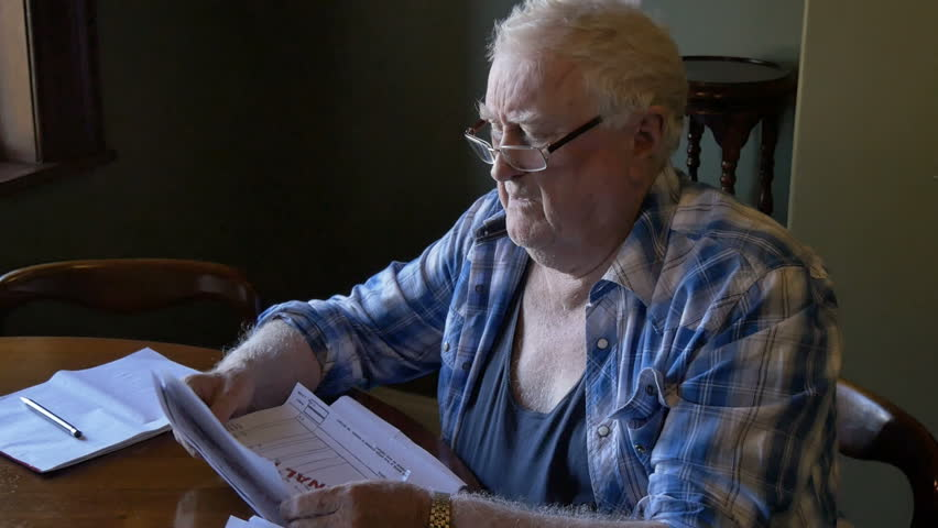 Elderly retired man sitting at desk looking at overdue bills