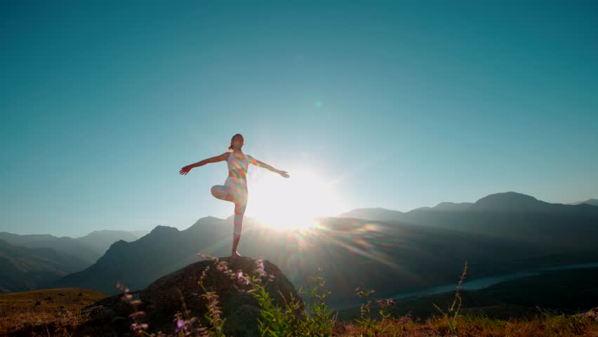 4K yoga in the mountains,a beautiful girl dressed in white ,sun,sun flare, slow motion