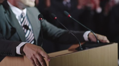 Closeup with selective focus of male politician hands lying on tribune as he delivering passionate speech before public, then making a fist and wildly gesturing