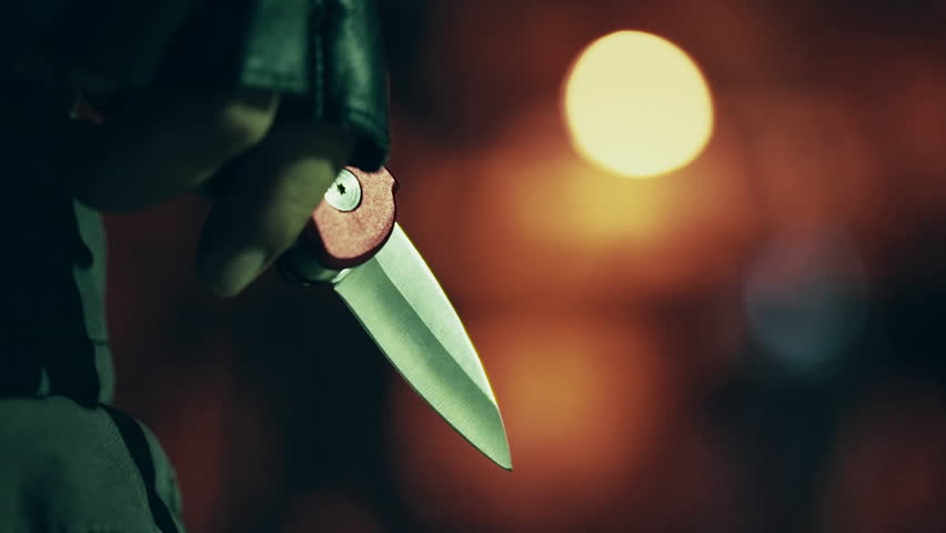 Killer with blade in hand shining at night.A hooded ominous figure stalking a residential building at night,his blade shining in the moonlight