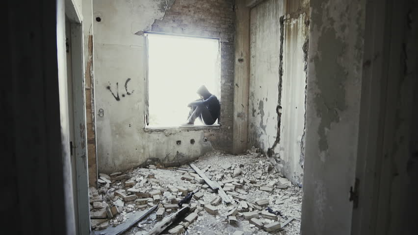 Hooded young man inside destroyed abandoned building,slow motion,dramatic.Young man facing social issues, inside a big wrecked empty building in 100fps slow motion.Camera gimbal motion.