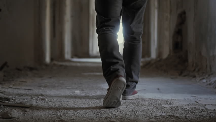 Hooded young man wondering inside destroyed abandoned building,slow motion,dramatic.Young man with social issues, walks inside a big wrecked empty building in 100fps slow motion.Camera gimbal motion.