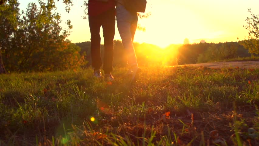 Happy joyful young couple walking in a park together, holding hands. Love, dating concept. Boyfriend takes hand of his girlfriend outdoors. Slow motion 240 fps, high speed camera. Full HD 1080p