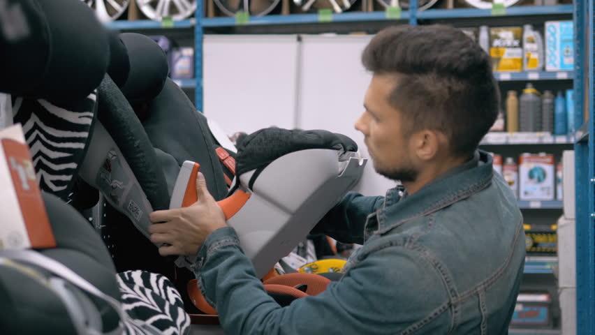 Customer choose child seat in supermarket. Man in car shop choosing children safety babyseat