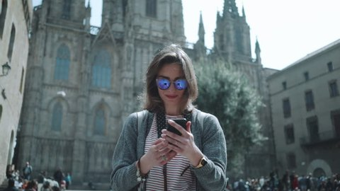 Young hipster traveler girl walking in the city and take picture via smartphone outside, attractive woman traveling at Europe looking landmarks in Barcelona, slow motion