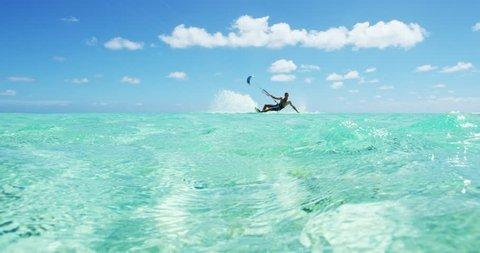 Young man kitesurfing in tropical blue ocean