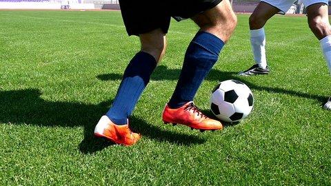 Footballer making tricks to avoid the defender, slow motion