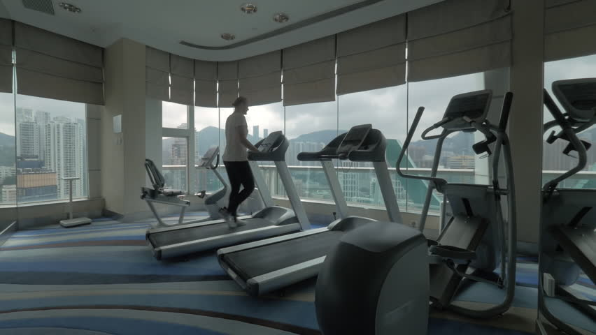 Clip of young blond woman going on the treadmill in fitness centre looking at window with modern building cityscape and then begin to run. Hong Kong, China | Shutterstock HD Video #19649986