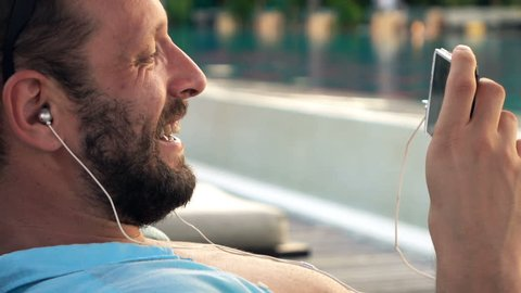 Happy man watching movie on smartphone lying on sunbed by pool