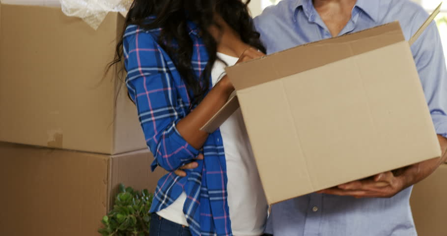 Young couple assisting each other while unpacking carton boxes in new house 4k | Shutterstock HD Video #19730776