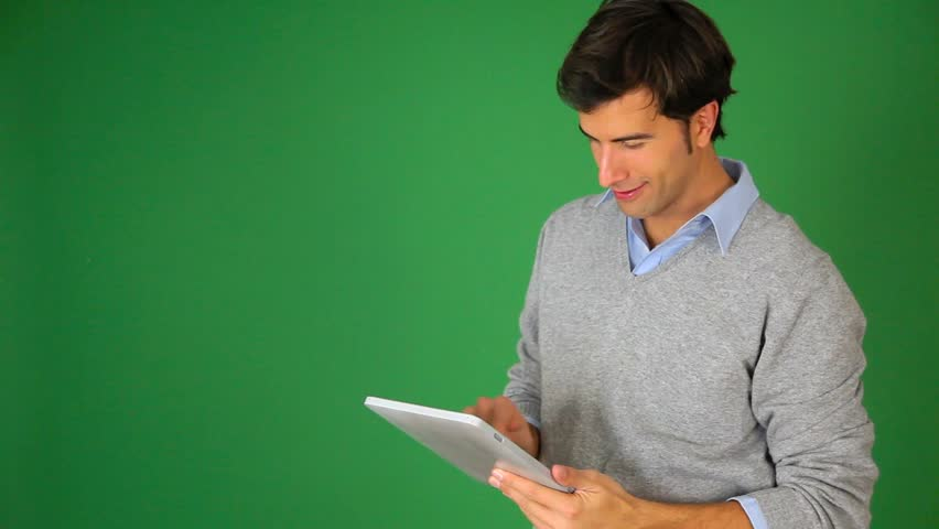Young man standing on green background with tablet