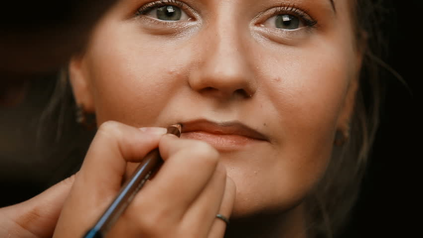 Make-up artist makes make-up young woman lips.Make-up artist doing make-up lip pencil to stroke the lips.Makeup. Cosmetic. Base for Perfect Make-up.Applying Make-up. Lips makeup