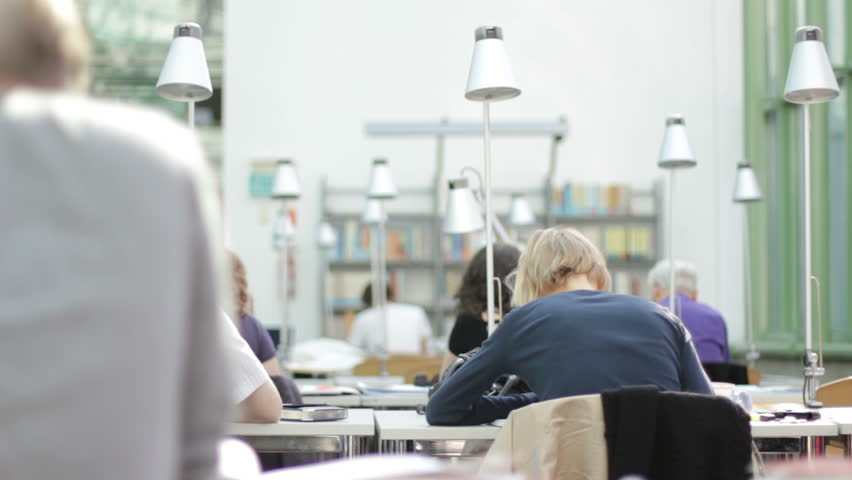 Student going through book pages in library | Shutterstock HD Video #1976086
