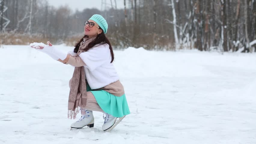 One girl sitting on her haunches at skating rink and throws snow