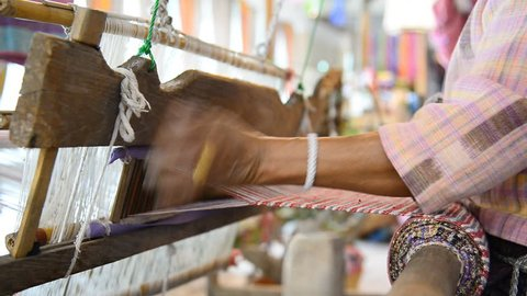 Traditional Thai textile manufacture in craft village, Old women work on wooden weaving thread machines and spin yarn creating cotton fabric. Chaing Mai, Thailand.