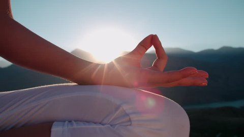4K beautiful girl in white clothes doing yoga in the mountains,sunrise,sun glare, close-up