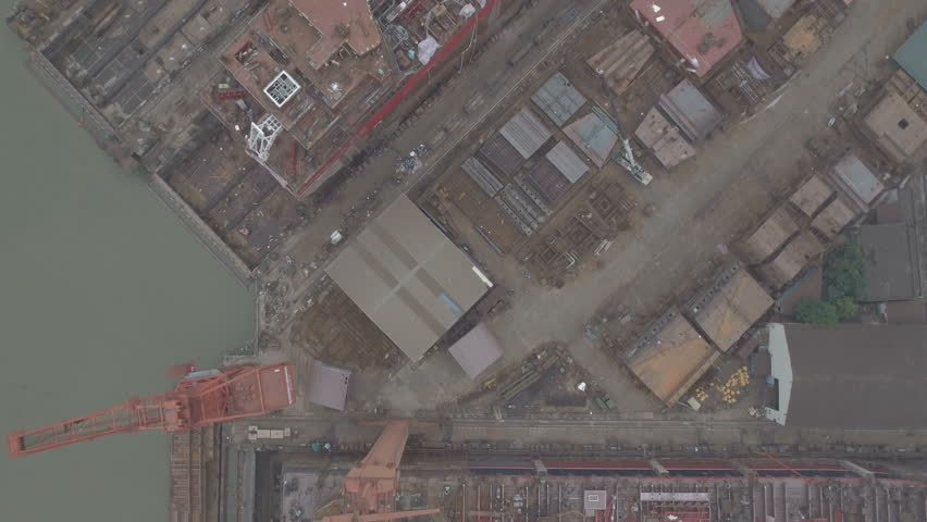 Overhead aerial view of an old and rusty shipyard in China. An example of a sector that helped fuel the country's economic growth, but appears to be struggling these days. D-log profile DJI Phantom.
