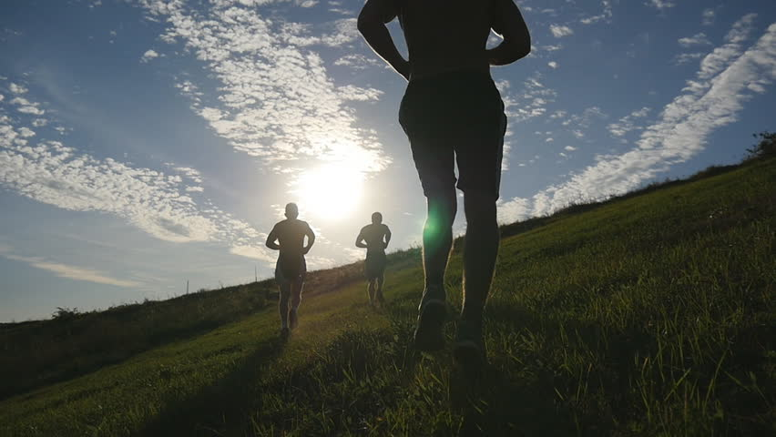 Young men running over green hill over blue sky background. Male athletes is jogging in nature at sunset. Sport runners jogging uphill outdoor at sunrise with flare. Cross-country training. Slowmotion | Shutterstock HD Video #19849144