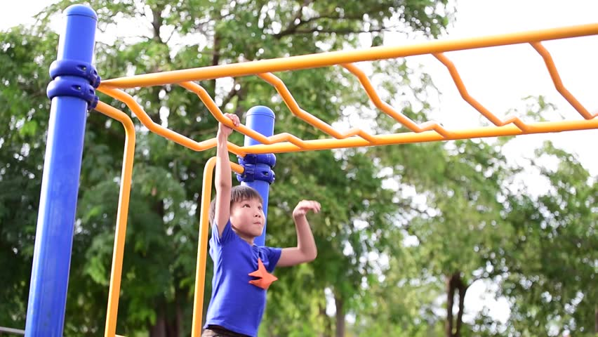 Slow motion, Young asian boy hang the yellow bar by his hand to exercise at out door playground under the big tree   Shutterstock HD Video #19852216