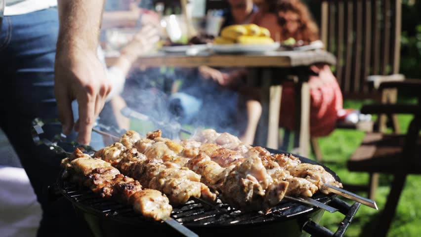 Leisure, food, people and holidays concept - man cooking meat on barbecue grill for his friends at summer outdoor party | Shutterstock HD Video #19884223