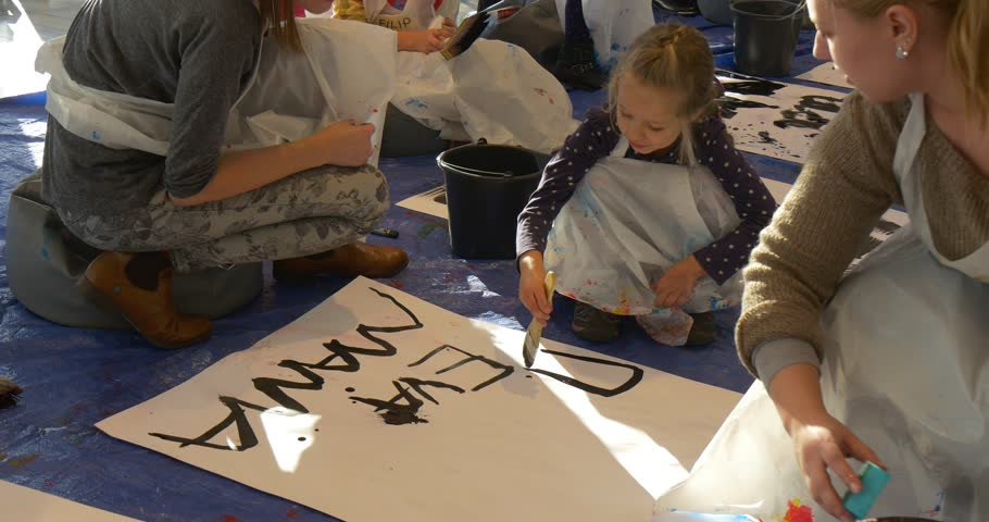 Woman, Mum or Educator Wipes the Paper Sheet With a Sponge, Kids Are Writing a Words on a Paper, Painting Black on Big Sheets of Paper. Little Blonde Girl With Braid. Kid is Holding a Big Brush and